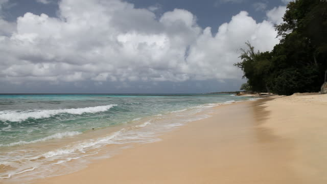 WS View of beach with ocean waves softly rolling on sunny day / Holetown, St. James, Barbados