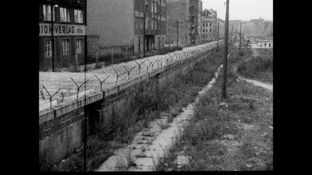 / view of Berlin Wall / East Berlin Checkpoint / flag waving in the wind against backdrop of buildings / Volkswagen Beetle drives up to checkpoint /...