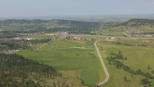 WS AERIAL TU View of bikers riding highway 170 and tilt up to reveal town / Sturgis, South Dakota, United States