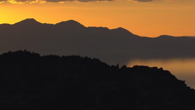 WS AERIAL View of blazing orange sunset behind mountains with reflection on great salt lake / Utah, United States