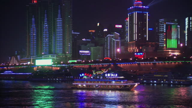 WS ZO View of boat and pretty city lights at night / Chongqing, Sichuan Province, China