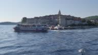 View of boat in Luka Korculanska Bay leaving Korcula Old Town, Korcula, Dalmatia, Croatia, Europe