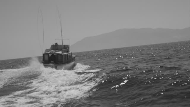 WS POV View of boat in ocean following behind fishing boat