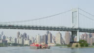 WS View of boat moving from under Barge & Manhattan Bridge / New York, United States