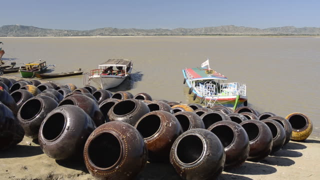WS View of Boats and large clay pots stored on banks of Ayeyarwadi river for loading / Bagan, Mandalay Division, Myanmar