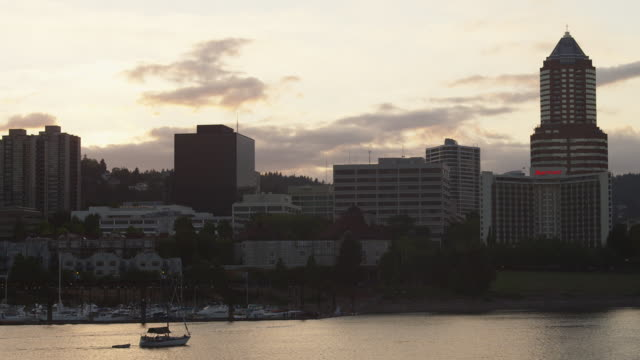 WS View of Boats pass in front of marina next to city of Portland with sun sets  / Portland, Oregon, United States