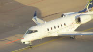 MS AERIAL ZO TS View of Bombardier Learjet airplane being pulling on tarmac / Wichita, Kansas, United States
