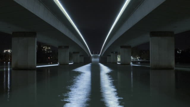 WS T/L ZO View of bridge and freeway underpass with traffic, lights reflecting in water at night / Canberra, Australian Capital Territory, Australia