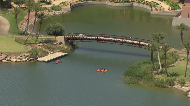 MS AERIAL View of bridge with two kayakers paddling in water of Lake Las Vegas with palm trees / Henderson, Nevada, United States