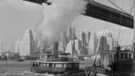 WS View of Brooklyn Bridge in foreground and city skyline in background with across East river boat enter foreground going away and Other boats moving in water