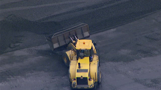 MS AERIAL View of bulldozer loading coal on coal train / Mandalong, New South Wales, Australia