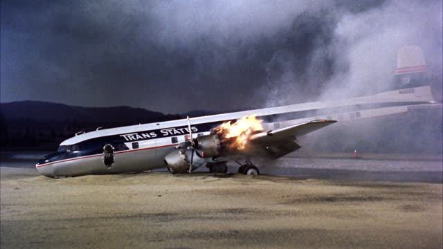 CU View of  burning engine of dc-6 four-engine propeller-driven passenger airplane landing on airport with fire wing