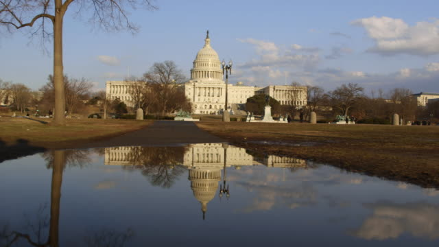 WS View of capitol building seen from the national mall and its reflection in rain puddle / Washington, District of Columbia, United States