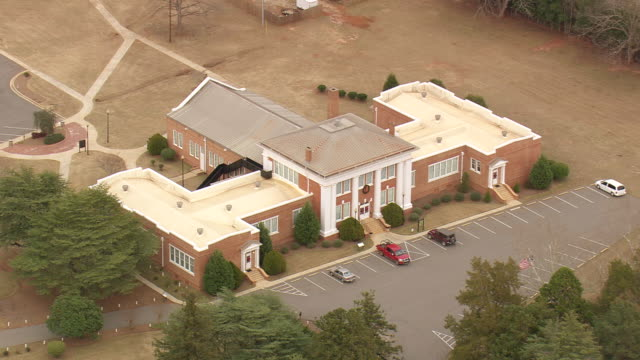 WS AERIAL View of Car parked in front of Plains high school / Georgia, United States