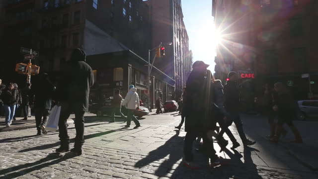 WS View of cars and pedestrians crosses shining Stone pavement street at SOHO / New York, United States