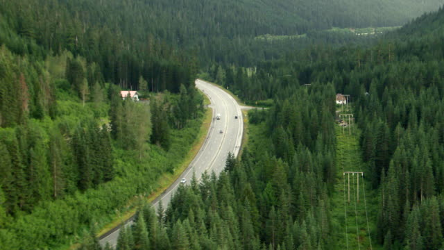WS AERIAL View of cars moving on curving Cascade Mountain Highway / Washington, United States
