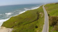 WS AERIAL View of cars running on California State Route 1 Highway as it hugs coastline / California, United States