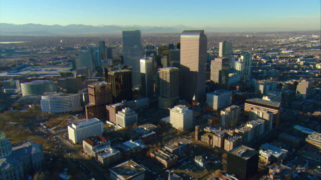 WS POV AERIAL View of central core of downtown Denver with Rocky Mountains behind / Denver, Colorado, USA