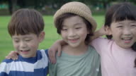 View of children with arm around laughing in summer at Seoulforest (the third largest park in Seoul city)