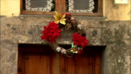 MS View of Christmas decorations on building wall and door / Tuscany, Italy