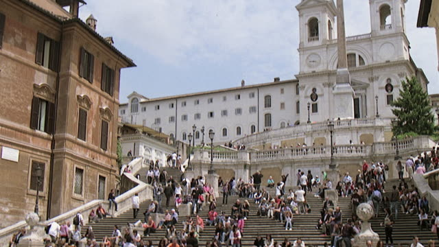 WS TU TD View of Church (Trinita dei Monti) with long and wide stairs many people moving and sitting on stairs and around fountain at Piazza di Spagna / Rome, Italy