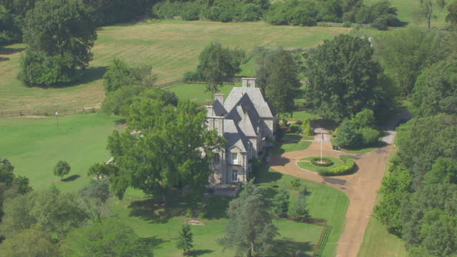WS AERIAL View of circle mansion with driveway and flag pole / Huntleigh, Missouri, United States
