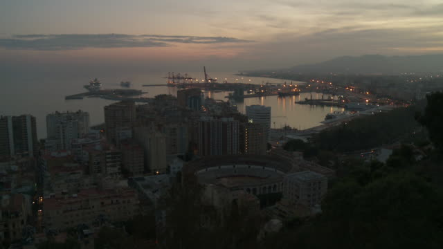 WS View of cityscape and harbour with ferry boats at dusk / Malaga, Andalusia, Spain