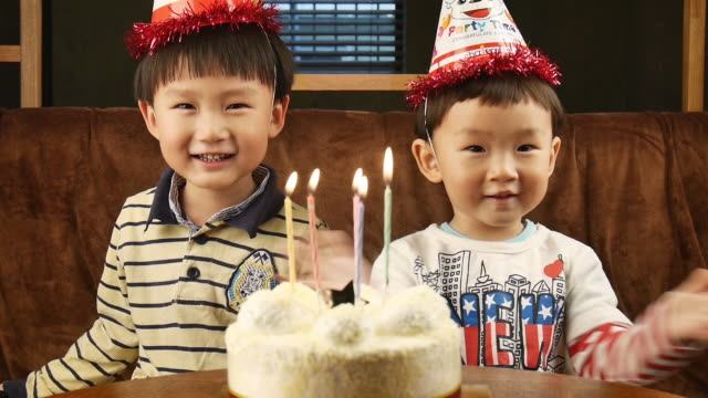 View of clapping boys behind of birthday cake