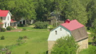 MS AERIAL DS View of classic red roofed farmhouse in Chase County with surrounded by trees / Kansas, United States
