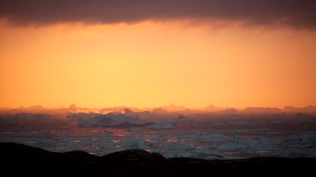 WS T/L View of cloud layer moving through orange sky over iceberg filled ocean / Ilulissat, Greenland