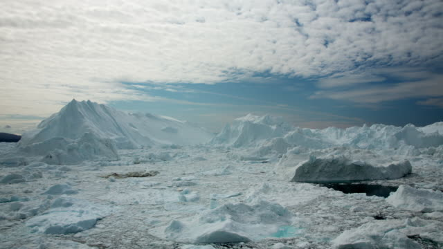 WS T/L View of clouds moving across sky, glacier and icebergs in ocean below / Ilulissat, Greenland