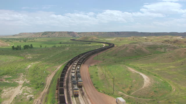 WS AERIAL View of Coal train traveling through green hills at Black Thunder Coal Mine / Wyoming, United States