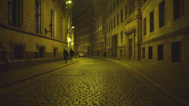 WS R/F View of Cobblestone Street with people at night / Riga, Latvia