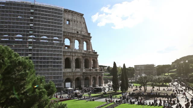 WS View of Coliseum with renovation works and scaffoldings, and people passing in street / Rome, Italy