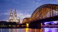 WS ZI T/L View of Cologne Cathedral with Hohenzollern Bridge and Rhine river at dusk / Cologne, North Rhine Westphalia, Germany