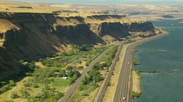 WS AERIAL View of Columbia River Gorge vast landscape with highway running along Columbia River / Oregon, United States