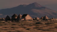 WS View of conical Chipaya homes in foreground in front of mountain peaks / Atahuallpa, Oruro, Bolivia