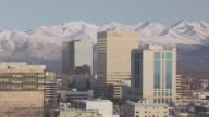 WS AERIAL DS View of Conoco Phillips building and downtown with mountains / Anchorage, Alaska, United States
