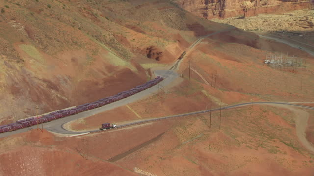 MS AERIAL ZO TS View of container loaded on truck and follow truck leaving mill tailing site in Moab / Utah, United States