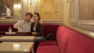 MS View of Couple sitting at table in restaurant pouring out their just served drinks / Toulouse, Haute Garonne, France