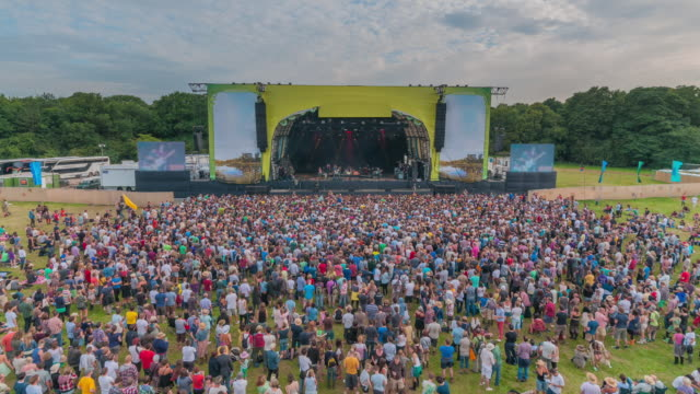 WS ZI T/L View of crowd watching bands perform at summer music festival / United Kingdom