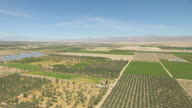 WS AERIAL POV View of cultivated farmland and ponds in desert valley with mountains in distance / California, United States