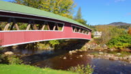 MS PAN View of Curved Covered Bridge with Wentworth Country Club in Northern New England in fall foliage in October / Jackson, New Hampshire, United States