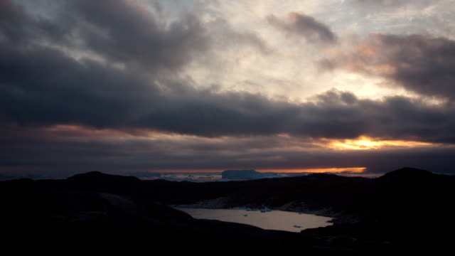 WS T/L View of dark clouds moving across sky and sun setting in distance with mountains and water below / Ilulissat, Greenland