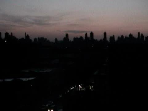 View of darkened Manhattan skyline at dusk during citywide blackout on August 14 2003 / Queens New York USA / AUDIO
