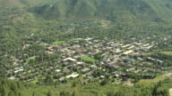 WS AERIAL View of dense trees on mountains, town buildings and streets / Aspen, Colorado, United States