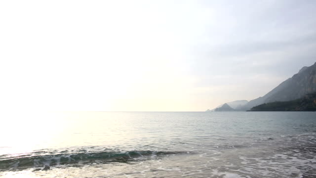 View of deserted beach and mountains, gentle surf