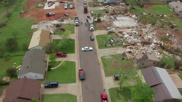 WS AERIAL View of Destroyed neighborhood houses with police in street and people cleaning up / Woodward, Oklahoma, United States