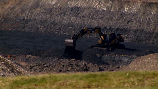 MS View of digger  in opencast mine seen through heathaze / Ffos-y-fran / Merthyr Tydfil, Glamorgan/Wales, United Kingdom