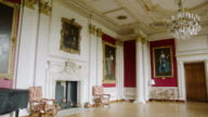 MS TD View of down to fireplace with portraits on walls at Kimbolton School / Cambridgeshire, United Kingdom